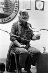 (32373) Utah Phillips Holding a Booklet and Speaking During a Performance, circa 1980