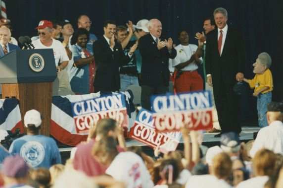 (32800) President Bill Clinton Laughs with child in Bill Clinton mask, 1996