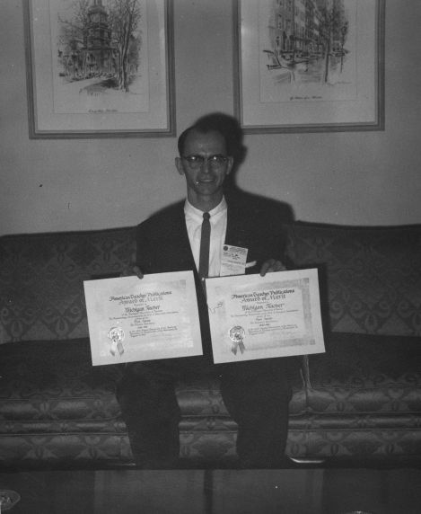 (11892) Henry Linne posing with awards